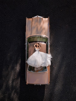 ピンクのレトロな車の屋根の上に横たわっているエレガントな花嫁の空撮