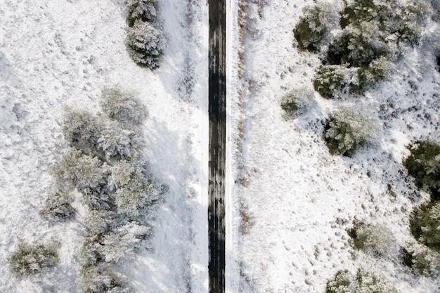 冬の森の空の雪に覆われた道路の航空写真。