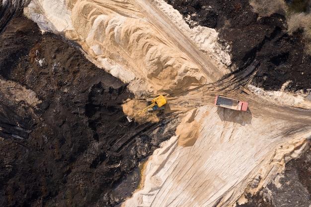 建設現場で働く掘削機とトラックの航空写真。