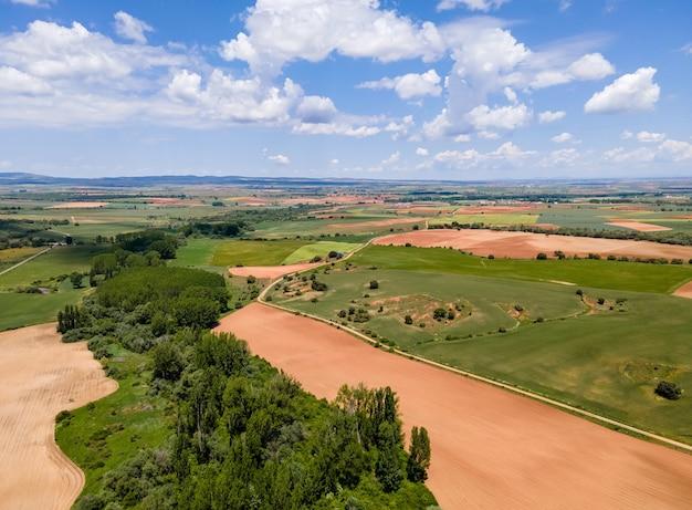 Аэрофотоснимок полей кастилии с сельскохозяйственными участками и голубым небом с облаками