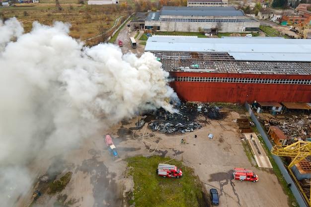 工業地帯で消火する消防士の航空写真。