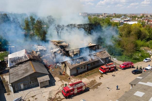 Вид с воздуха на пожарных, тушащих разрушенное здание в огне с обрушенной крышей и поднимающимся темным дымом.