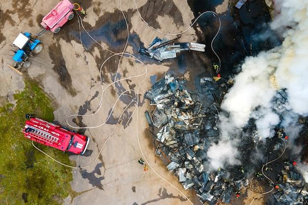 工業地帯にある古い工場の近くで消火活動をしている消防士の航空写真。