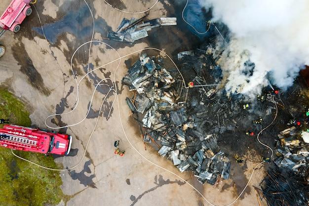 工業地帯にある古い工場の近くで火事と戦っている消防士の航空写真。