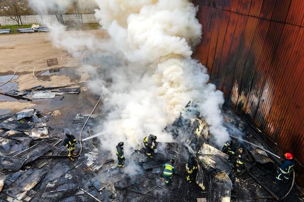 工業地帯の古い工場の建物の近くで火と戦っている消防士の航空写真。