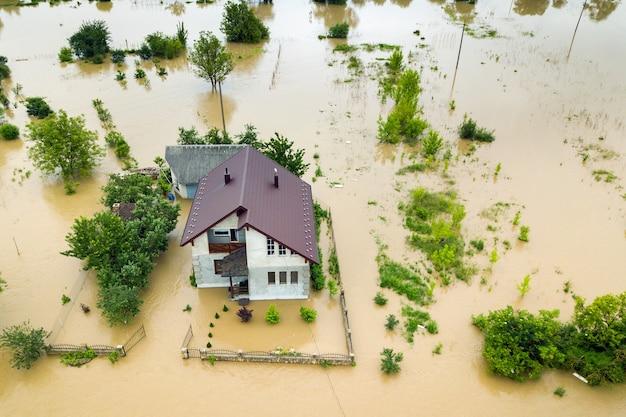 Вид с воздуха на затопленный дом с грязной водой