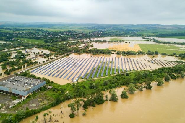 雨季に汚れた川の水で浸水太陽光発電所の空撮。