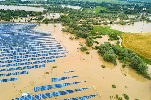 雨季に汚れた川の水で浸水した太陽光発電所の航空写真。