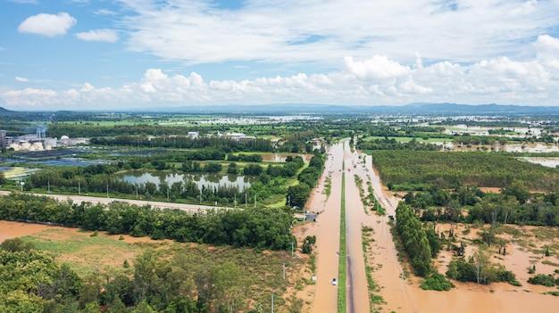 자동차가 있는 침수된 마을과 시골길의 공중 보기, 드론으로 촬영한 위에서 보기