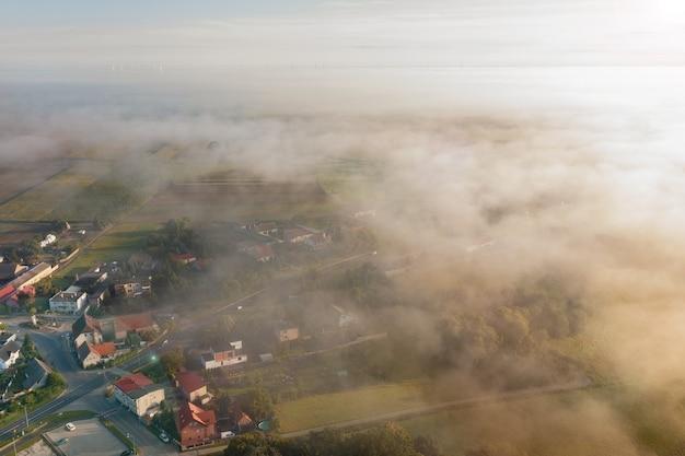 Вид с воздуха на туманное осеннее поле и лесной пейзаж. вид на маленькую деревню утром, дрон