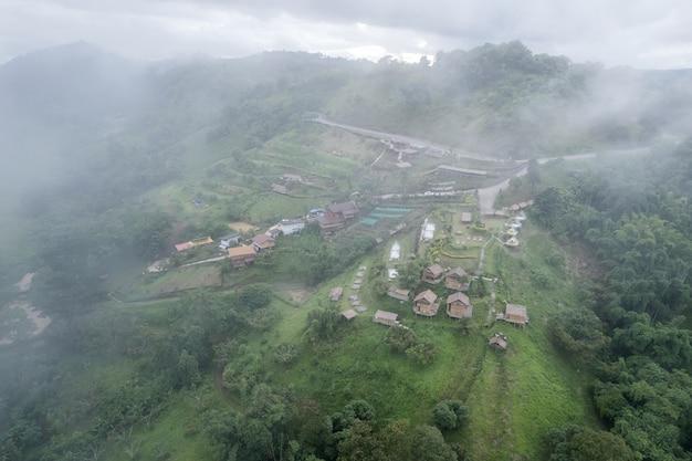 Вид с воздуха на туманную гору и хижину курорта на склоне холма в тропических лесах в дождливый день в таиланде