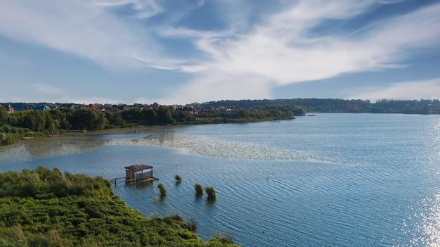 숲과 푸른 호수의 공중 전망입니다. 낚시 보트와 목재 부두입니다.