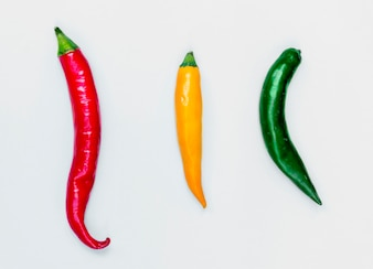 Aerial view of fresh red green yellow chili peppers on white background