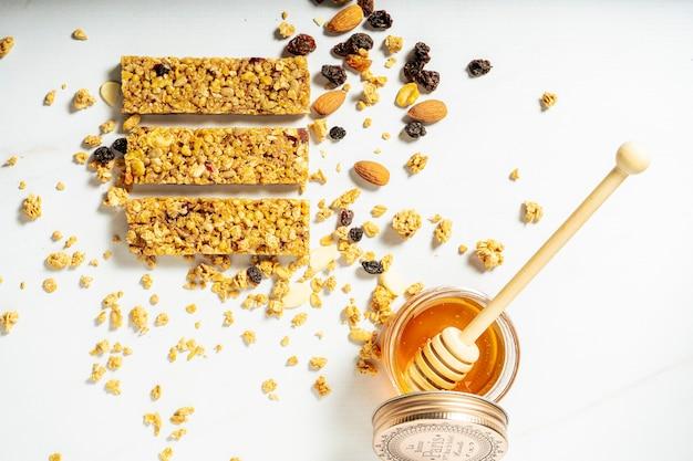 白い表面に天然蜂蜜の瓶とドライフルーツとレーズンのグラノーラまたはシリアルバーの空撮。健康的で自然な食事の概念。