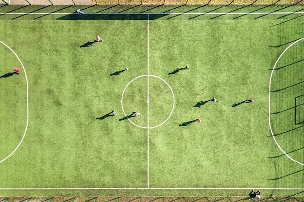 Аэрофотоснимок зеленой футбольной спортивной площадки и игроков, играющих в футбол