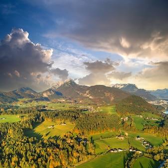 オーストリアのアルプス山脈の村や森と緑の牧草地の空撮