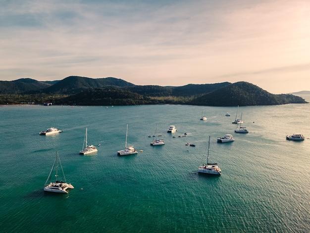 Вид с воздуха на группу частных яхт, путешествующих по тропическому морю вечером