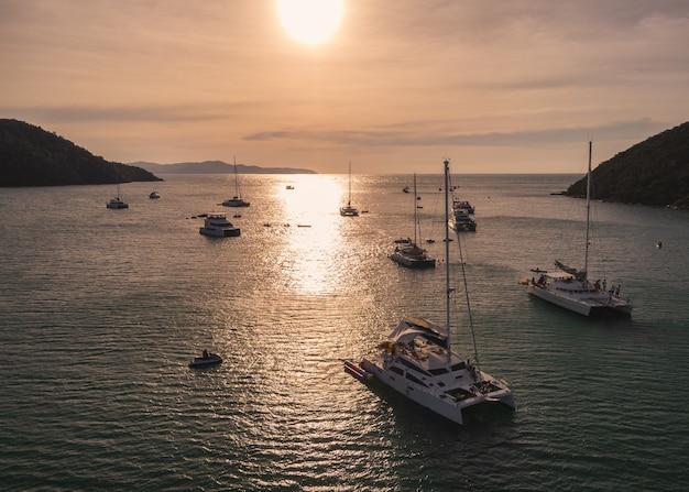 日没時に熱帯の海を航行するプライベートヨットのグループの航空写真