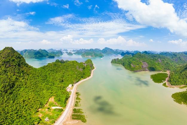 Вид с воздуха на залив халонг от острова ба ба, известного туристического направления во вьетнаме. сценарное голубое небо с облаками, пики известковой скалы в море на горизонте.