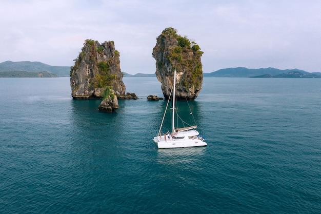 Вид с воздуха на счастливых тысячелетних друзей, отдыхающих на парусной яхте в морском путешествии по океану