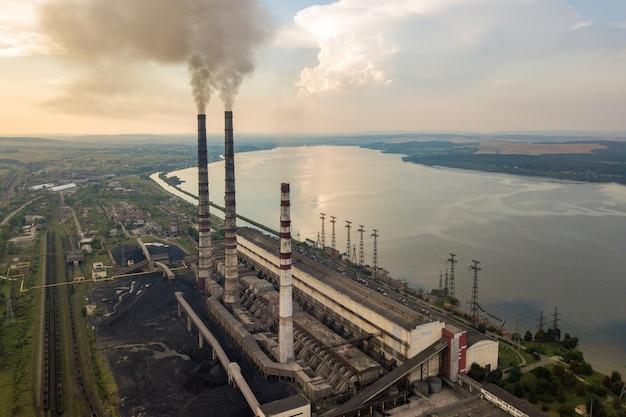 石炭発電所からの灰色の煙と高い煙突パイプの空撮。化石燃料による発電。