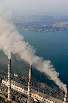 石炭火力発電所からの灰色の煙で高い煙突パイプの航空写真。化石燃料による発電。