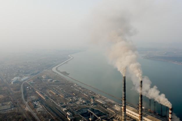 石炭火力発電所からの灰色の煙で高い煙突パイプの航空写真