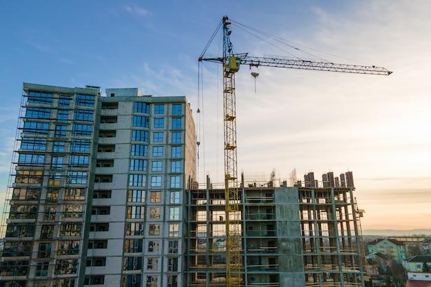 석양에 건설 중인 고층 타워 크레인과 주거용 아파트 건물의 공중 전망. 부동산 개발.