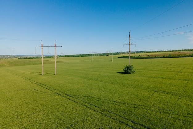 봄철 송전선에서 녹색 밀밭 위를 날아다니는 고전압 전기 타워와 밀밭 위를 나는 현대 농업 드론의 공중 전망