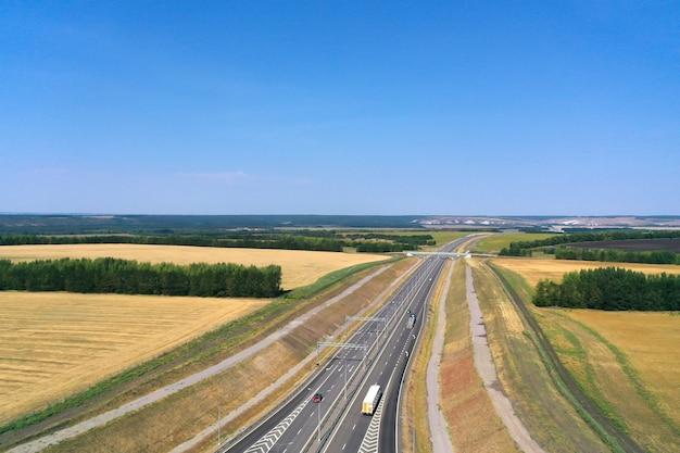 Вид с воздуха на шоссе вдоль сельскохозяйственных полей