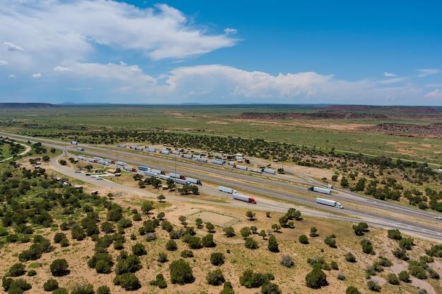 자동차 트럭의 애리조나 사막에 있는 고속도로의 공중 전망은 끝없는 고속도로 근처에 대형 주차장이 있는 휴게소를 중지합니다.