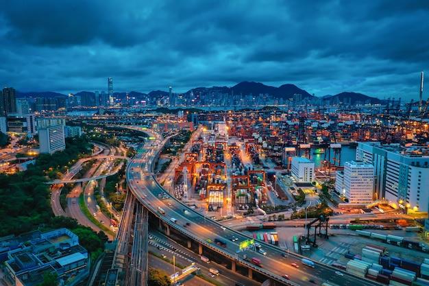 Вид с воздуха города гонконга с стержнем порта контейнера на драматическом небе в гонконге.