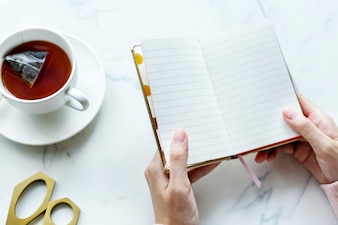 Aerial view of hot tea drink and woman holding blank journal copy space