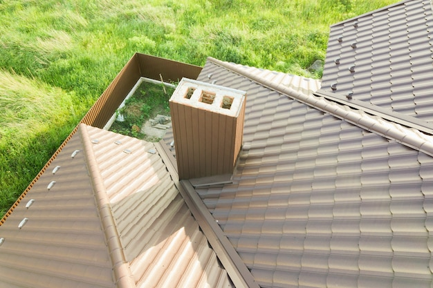 갈색 금속 타일 시트로 덮인 집 지붕 구조의 공중 전망.