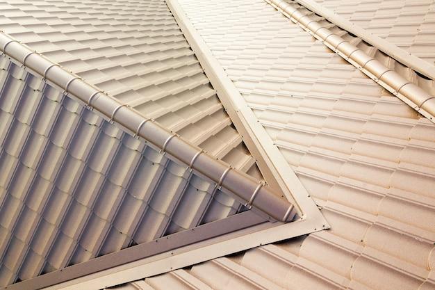 Вид с воздуха на конструкцию крыши дома, покрытую коричневыми листами металлочерепицы.