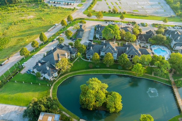 Вид с воздуха на хьюстон, техас, сша. типовая многоуровневая квартира с прудом, в окружении зеленого сада машин на парковках