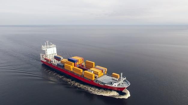 Вид с воздуха на огромный контейнеровоз, плавающий в море