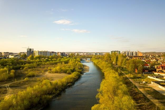 Bystrytsia川と遠くに建設中の高い住宅の建物があるウクライナのイバノフランコフスク市の航空写真。