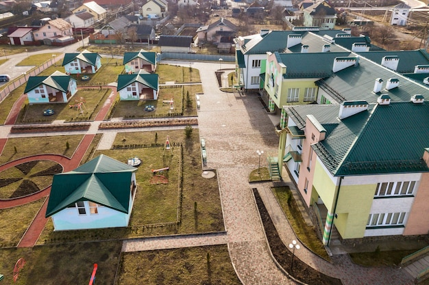Вид с воздуха на детский сад или современный школьный комплекс, украшенные крыши зданий и красочную игровую площадку на солнечном дворе.