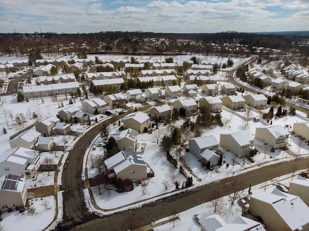 屋根付きの家や道路に雪が降る冬の町の住宅の風景トップの空撮。