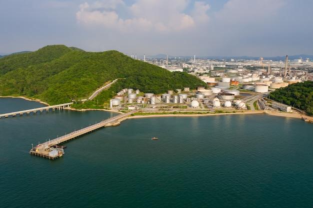 Вид с воздуха на большие резервуары для хранения топлива в промышленной зоне нефтеперерабатывающего завода и море с мостом на переднем плане в таиланде
