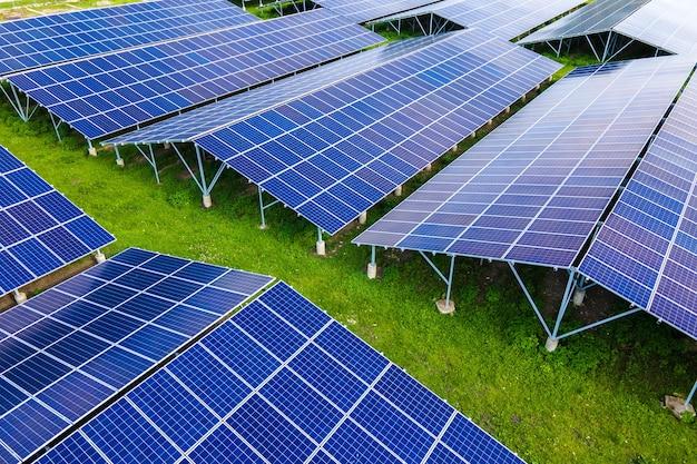 クリーンな生態学的電気エネルギーを生成するための太陽光発電パネルの列を備えた大規模で持続可能な発電所の航空写真。ゼロエミッションコンセプトの再生可能エネルギー。