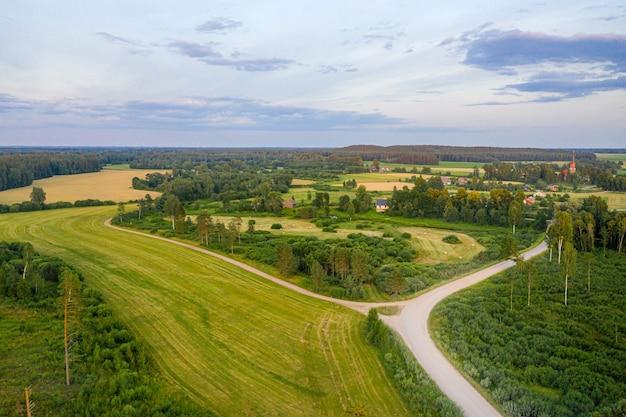 Аэрофотоснимок латвийского сельского пейзажа с сельскохозяйственными полями, лесами и дорогами на закате