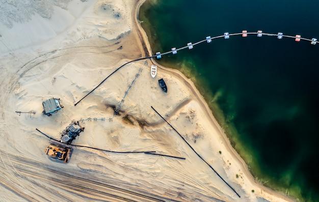 Вид с воздуха машин и шахтного оборудования возле глубокого синего озера