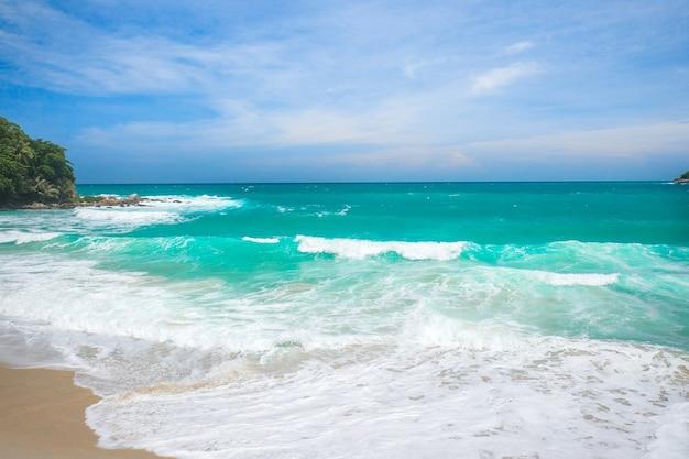 ビーチで彼の手で波をキャッチする男の空撮
