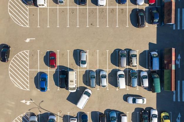Аэрофотоснимок многих красочных автомобилей, припаркованных на стоянке с линиями и разметкой для парковочных мест и направлений.