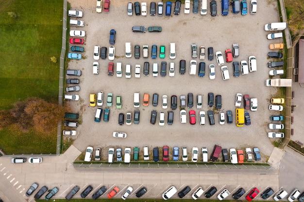 Вид с воздуха на множество красочных автомобилей, припаркованных на общественной стоянке.