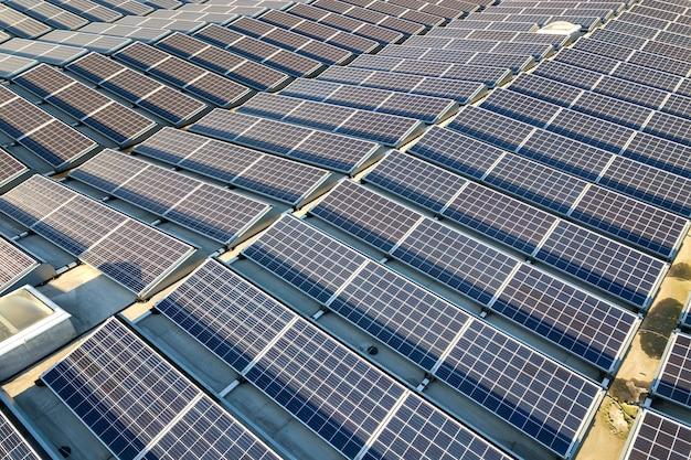 Вид с воздуха на многие фотоэлектрические солнечные панели, установленные на крыше промышленного здания.