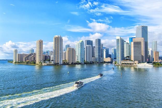푸른 흐린 하늘, 마이애미 시내 옆에 항해하는 흰색 보트와 마이애미 고층 빌딩의 항공 보기