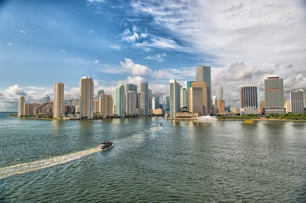 青い曇り空、マイアミのダウンタウンの隣を航行する白いボートとマイアミの高層ビルの空撮